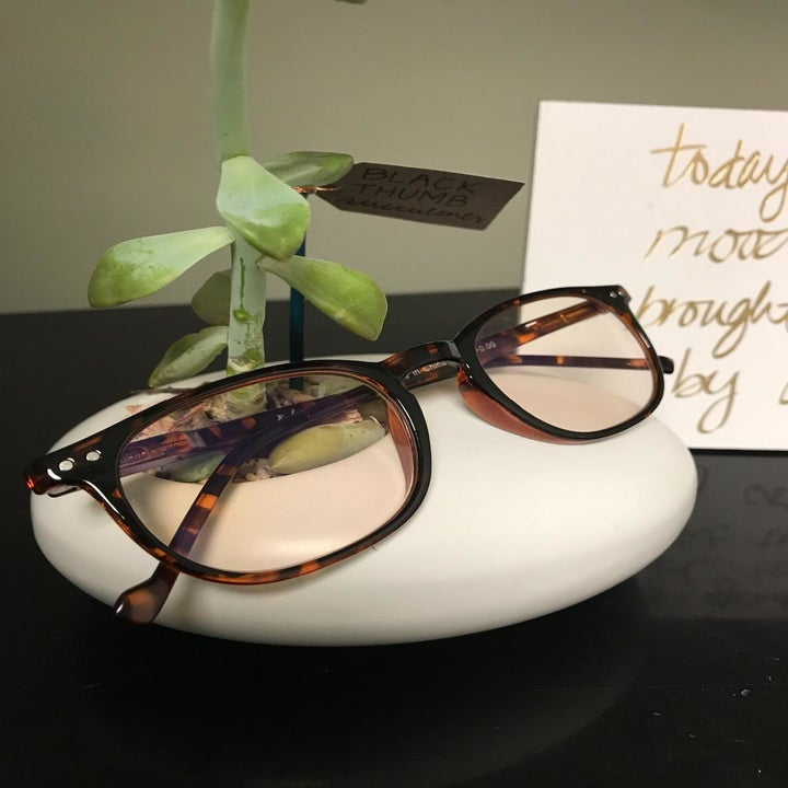 A reviewer photo of a pair of blue light glasses sitting on a desk next to a small plant