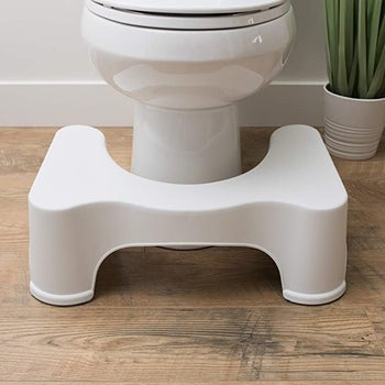 A toil with the white Squatty Potty sitting in front