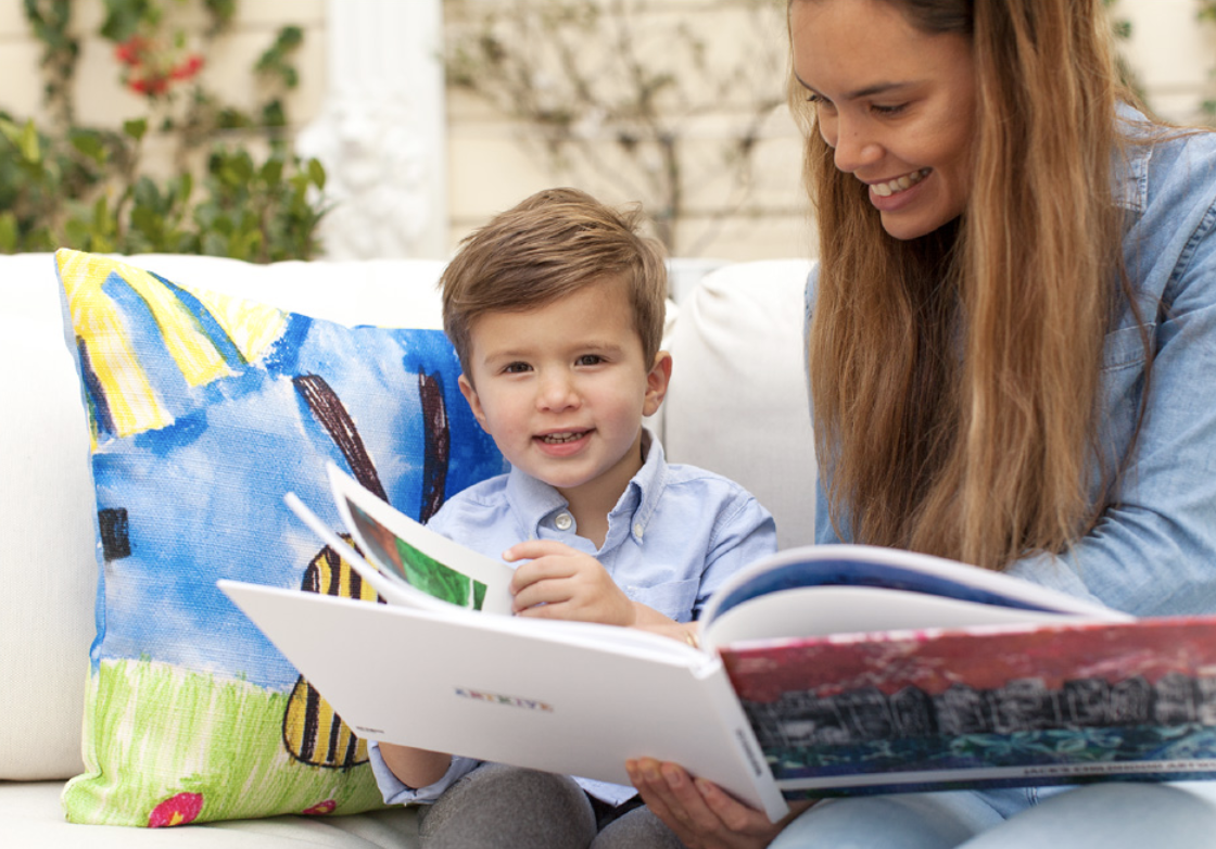 a mother and child reading a book of the child's art