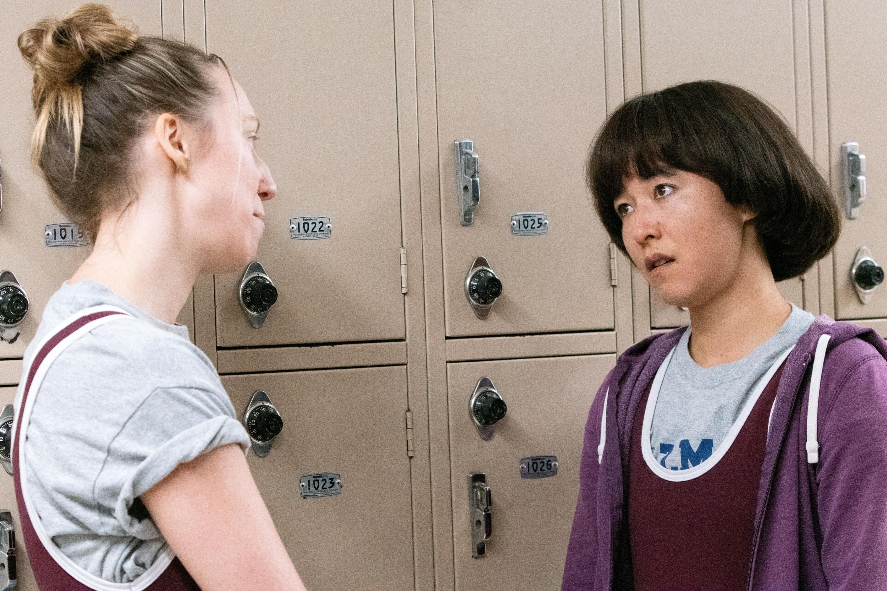 "Anna Konkle and Maya Erskine talking by a set of lockers while wearing wrestling jerseys in the PEN15 episode ""Wrestle"""