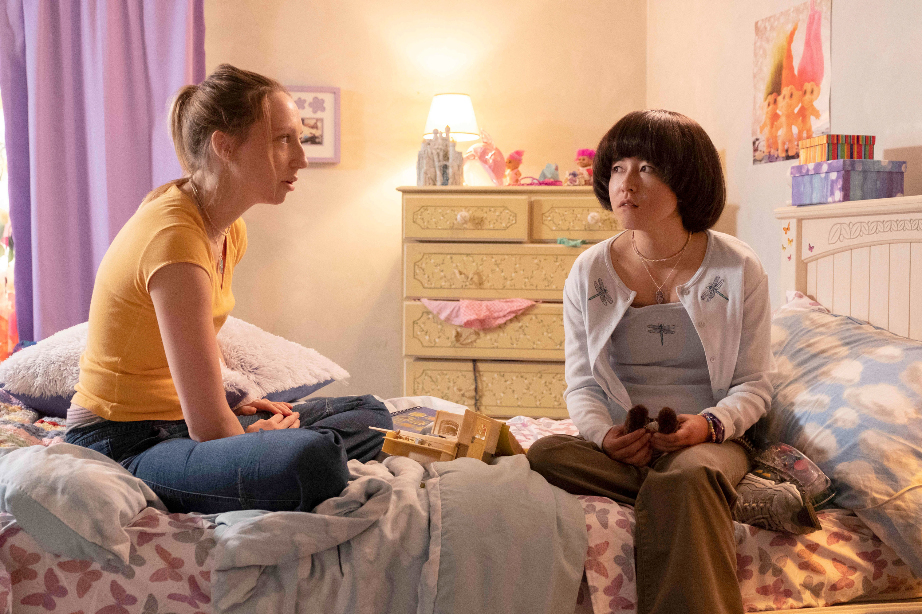 Anna Konkle, in a shirt and blue jeans, sits on a bed across from Maya Erskine, in a top and cardigan with firefly patterns on them