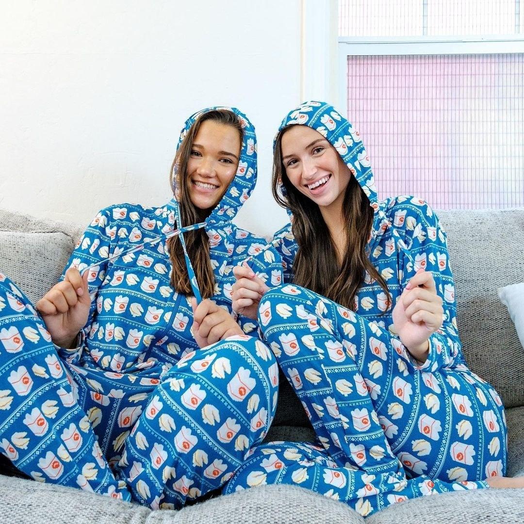 two models wear hooded onesies in takeout food pattern