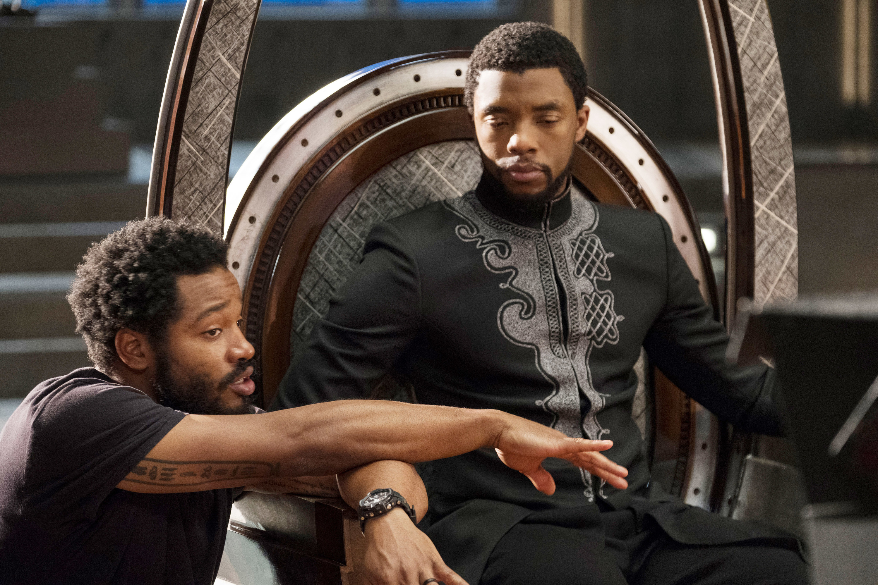 Chadwick Boseman sitting on a throne as T'Challa listening to direction