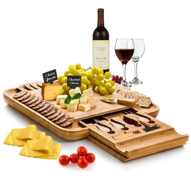 wooden cheese board loaded with cheese and fruit