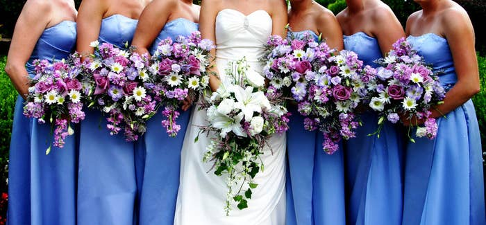 A bride's bouquet surrounded by her bridesmaids holding theirs