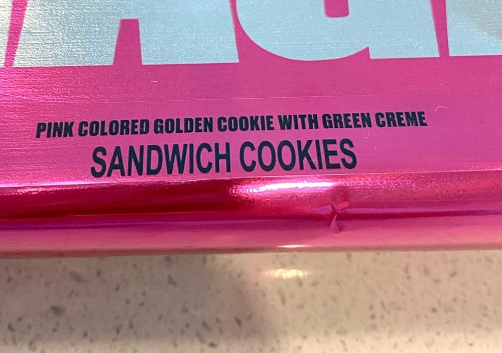 """A close-up of the packaging saying, """"pink colored golden cookie with green creme"""""""