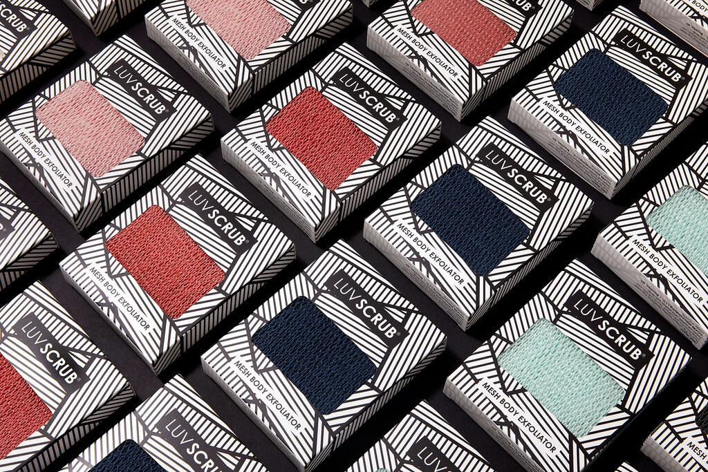The scrubs in orange, mint, pink and navy blue in their packaging