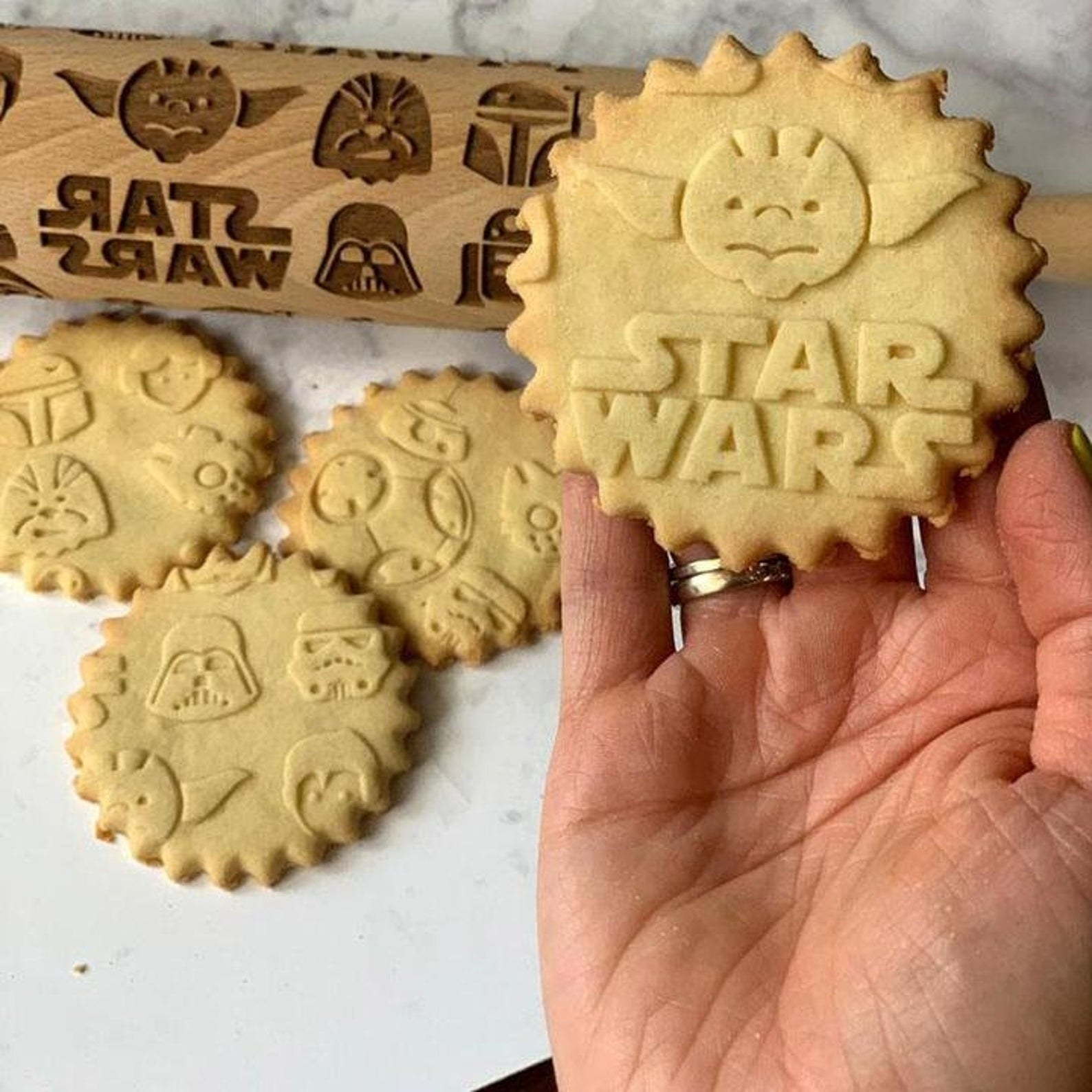 the star wars dough roller and cookies with various imprints on them made using the roller