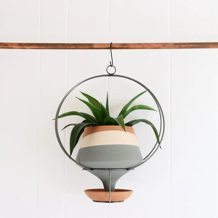 planter with long funnel spout held in a circular metal holder with little terracotta dish under the sprout
