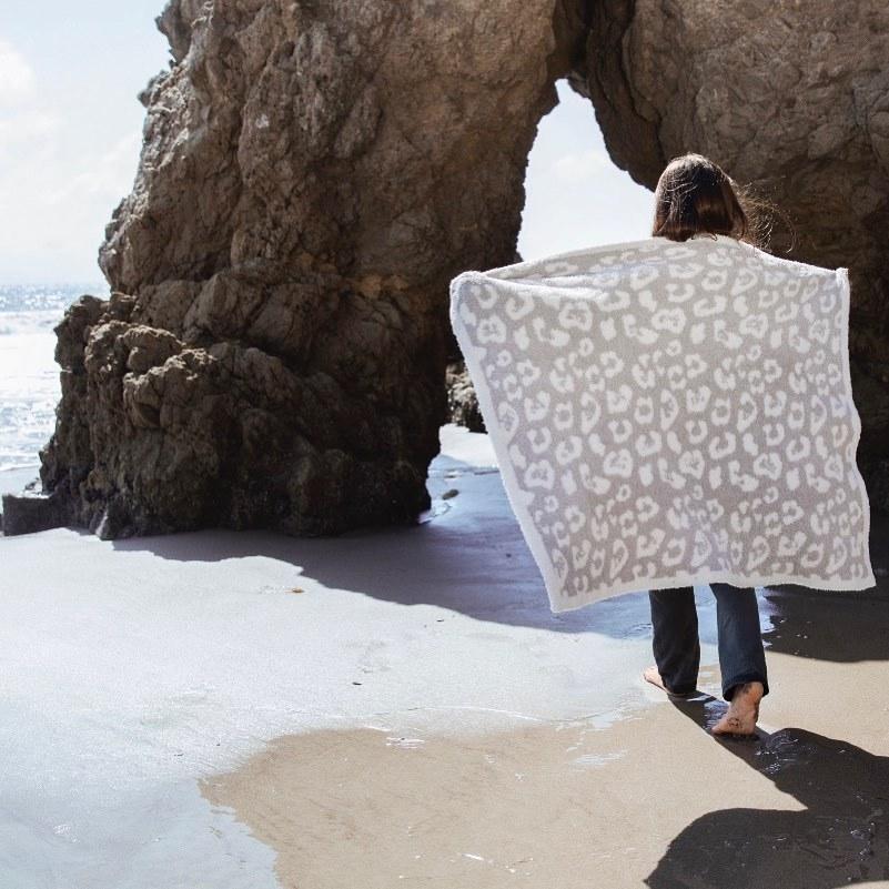 person walking on beach wrapped in leopard print blanket