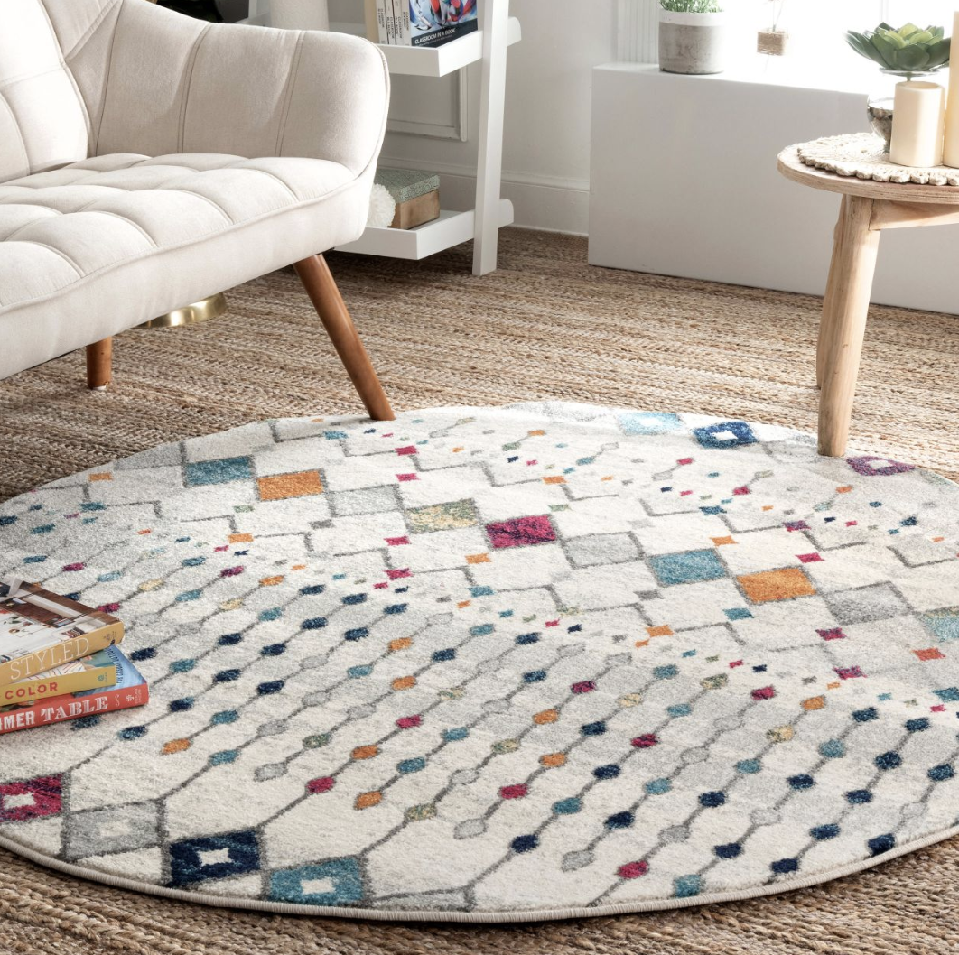 A round white rug with asymmetrical diamond and line patterns with rainbow accents
