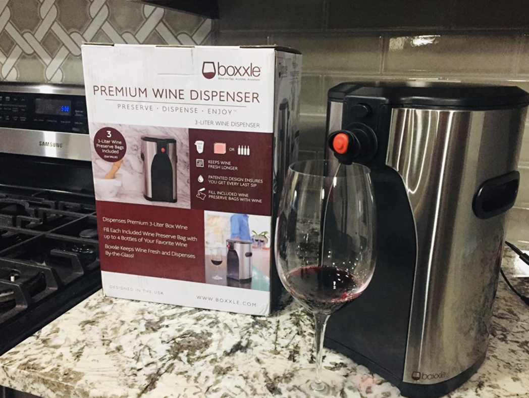 reviewer pic of the silver sleek wine dispenser on a counter, with a wine glass in front of it, pouring red wine into it