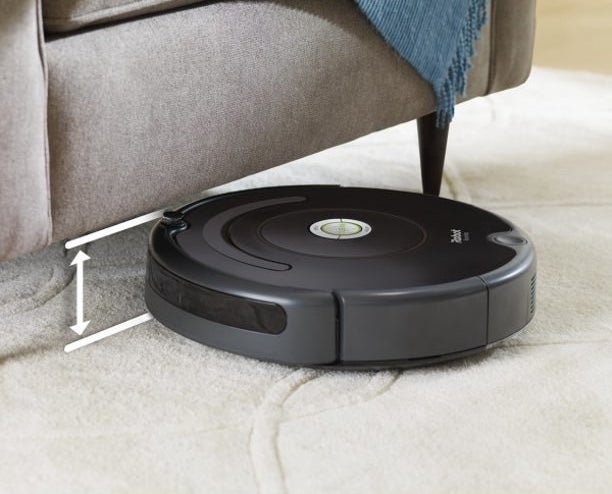 robot roomba vacuum going underneath a couch