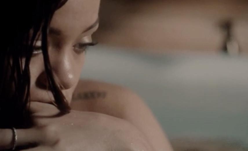 Rihanna looking sad in a bathtub.