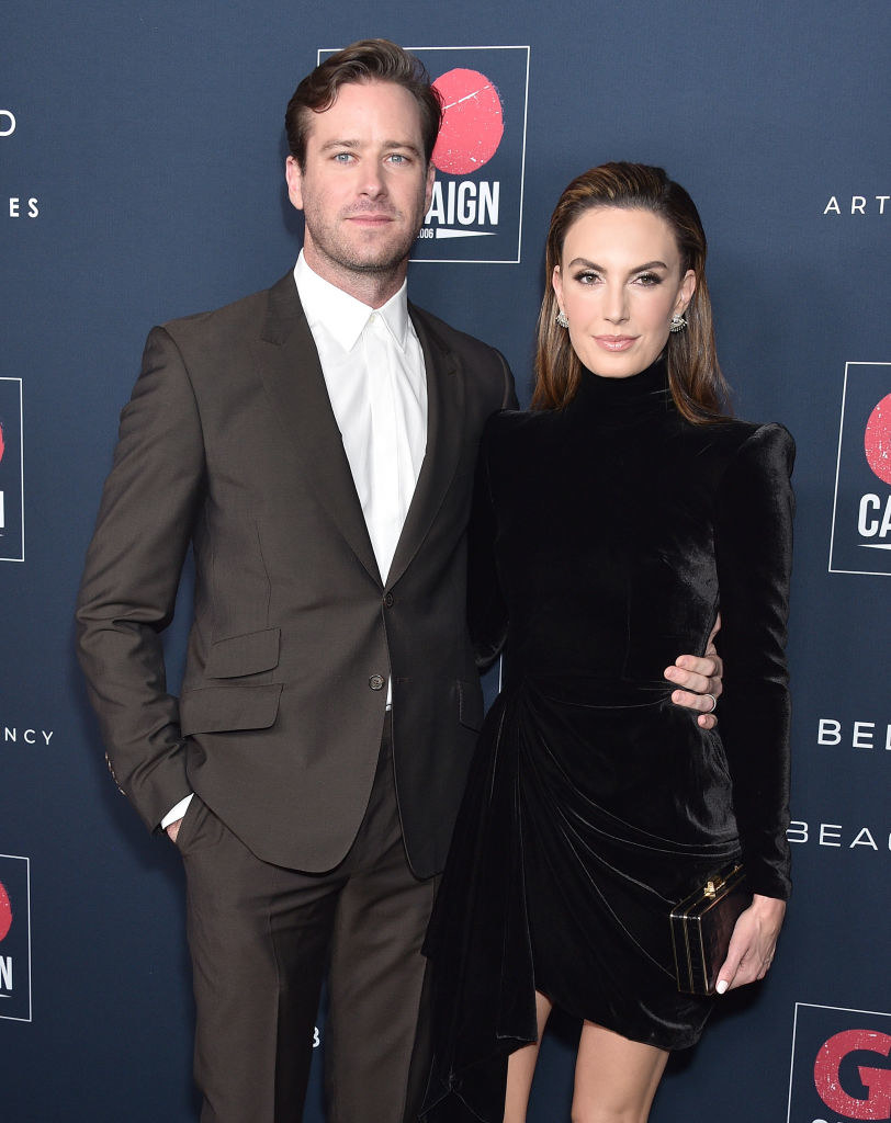 Armie, wearing a suit, and Elizabeth Chambers, wearing a short velvet dress and carrying a clutch, pose on a red carpet