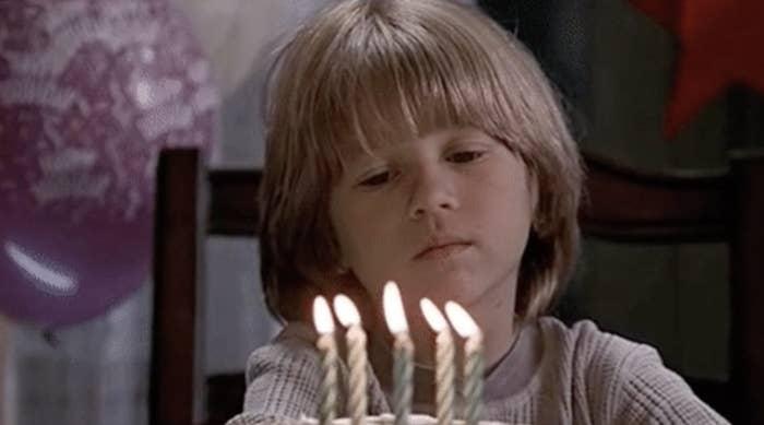 Kid looking sad at a birthday candle.