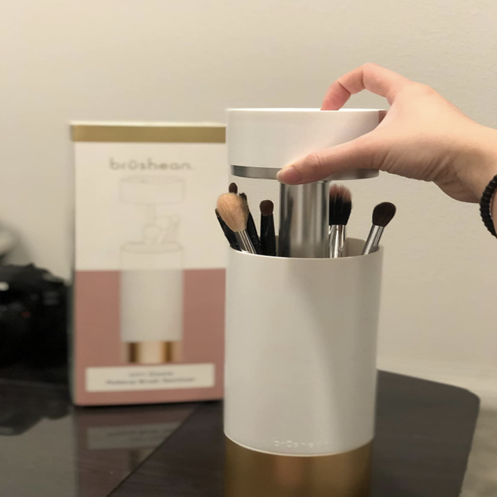 a different reviewer showing how easy it is to lift the top and put makeup brushes into the sanitizer