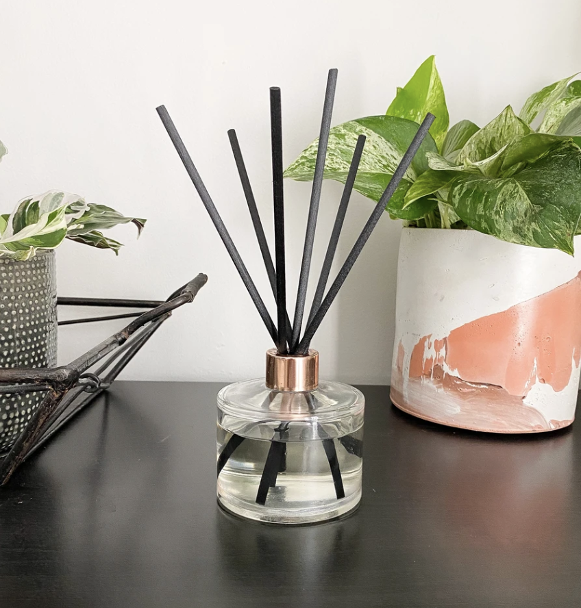 A glass reed diffuser with a gold accent at the rim on a desk