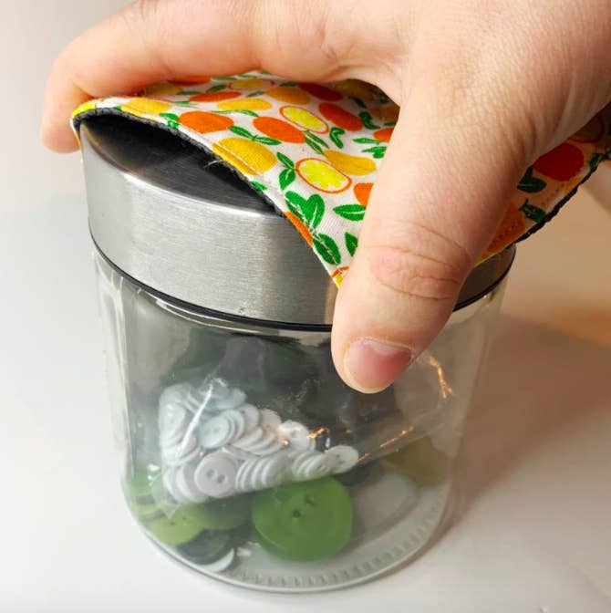 A person using the pad to open a jar of sewing supplies