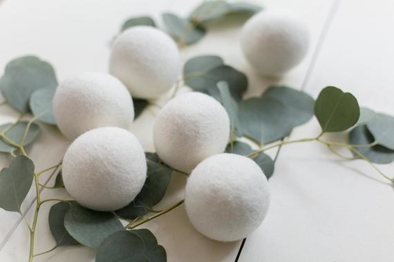 Six wool dryer balls sitting atop a vine