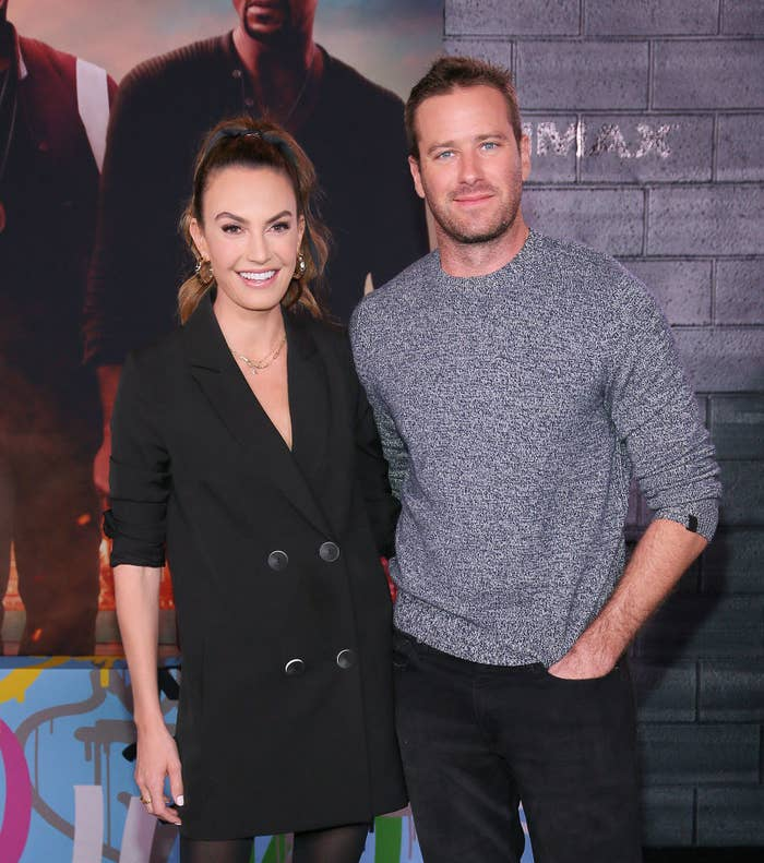 Elizabeth Chambers, wearing a blazer dress and pantyhose, and Armie smile as they pose for photos on a red carpet