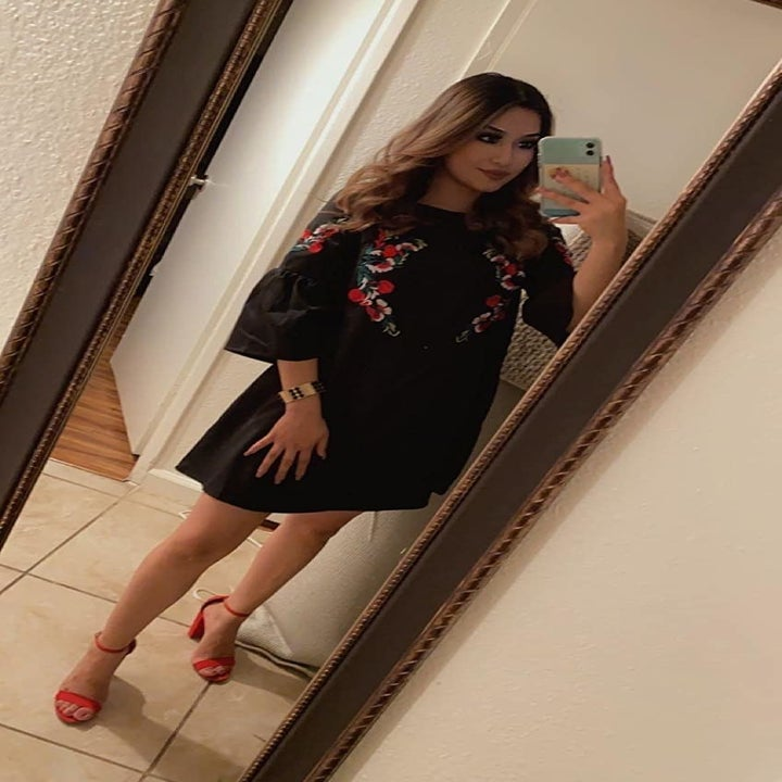 A reviewer wearing the dress in black with floral embroidery