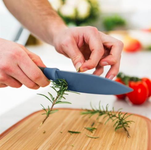 Someone pulling a stem of rosemary through the herb stripper holes at the base of the knife