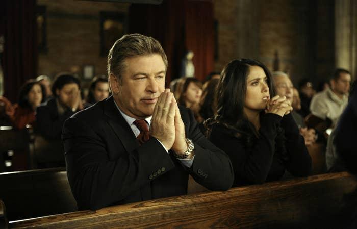 "Alec Baldwin and Salma Hayek pray at a church in the 30 Rock episode ""Saint Valentine's Day"""