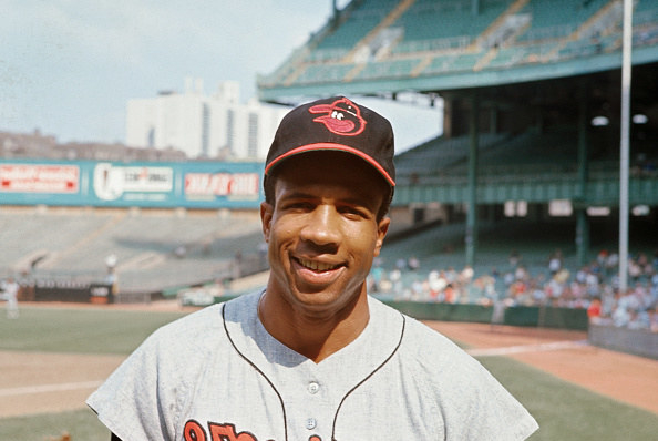 Frank Robinson in Orioles jersey and hat.
