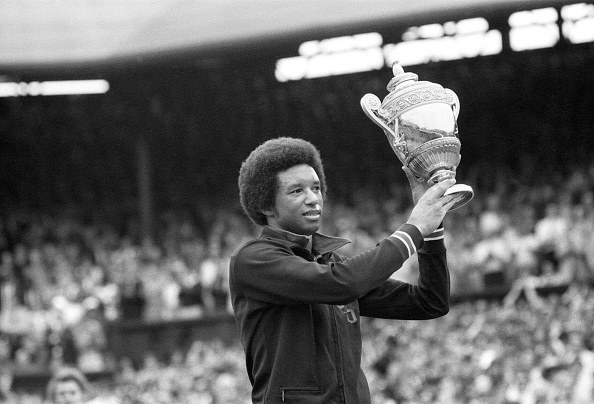 Arthur Ashe holding Wimbledon trophy