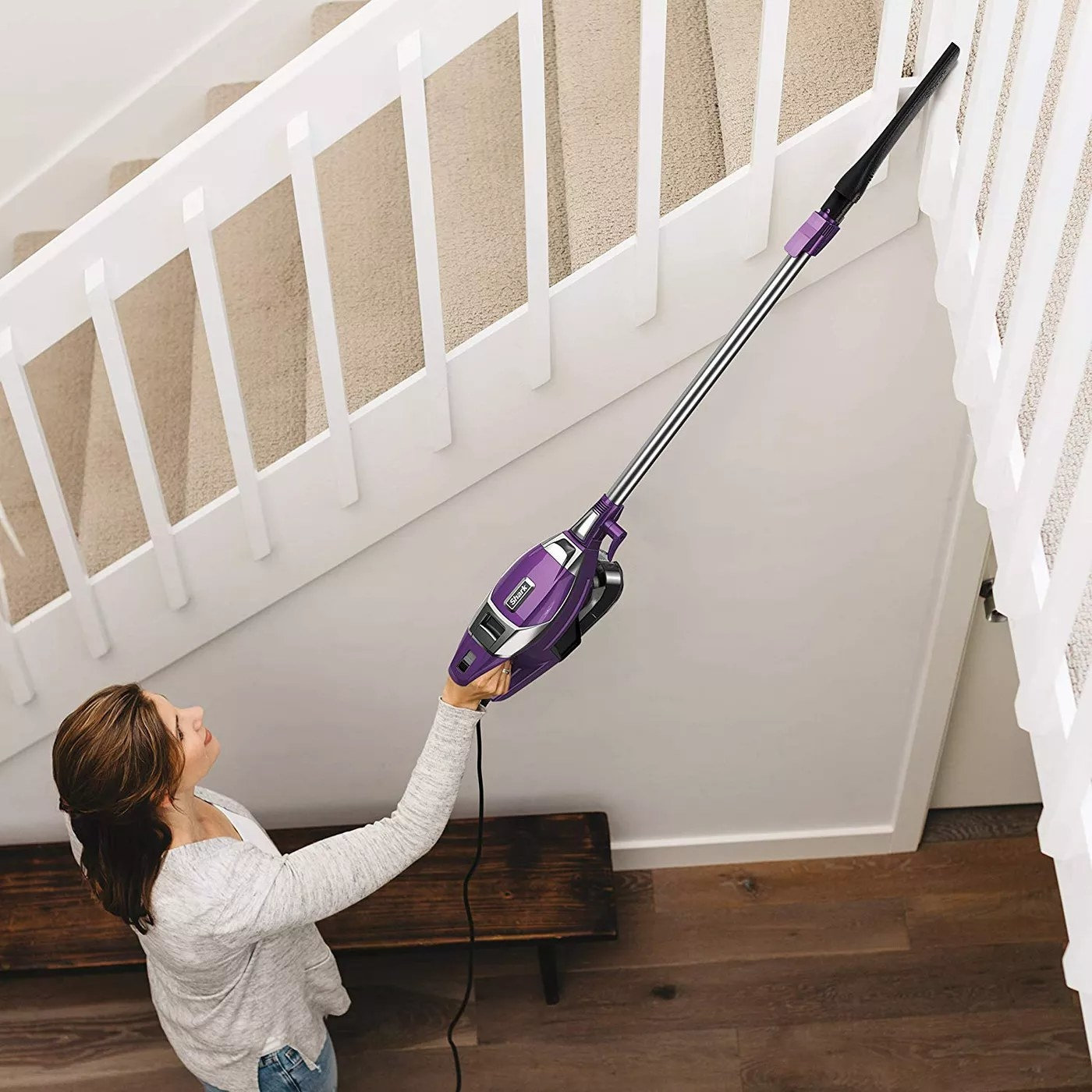 A model using the stick vacuum to clean the top of some stairs