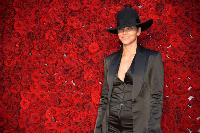 Halle Berry wears a black blazer and a black hat in front of a wall of red flowers at the grand opening gala at Tyler Perry Studios in Atlanta, Georgia