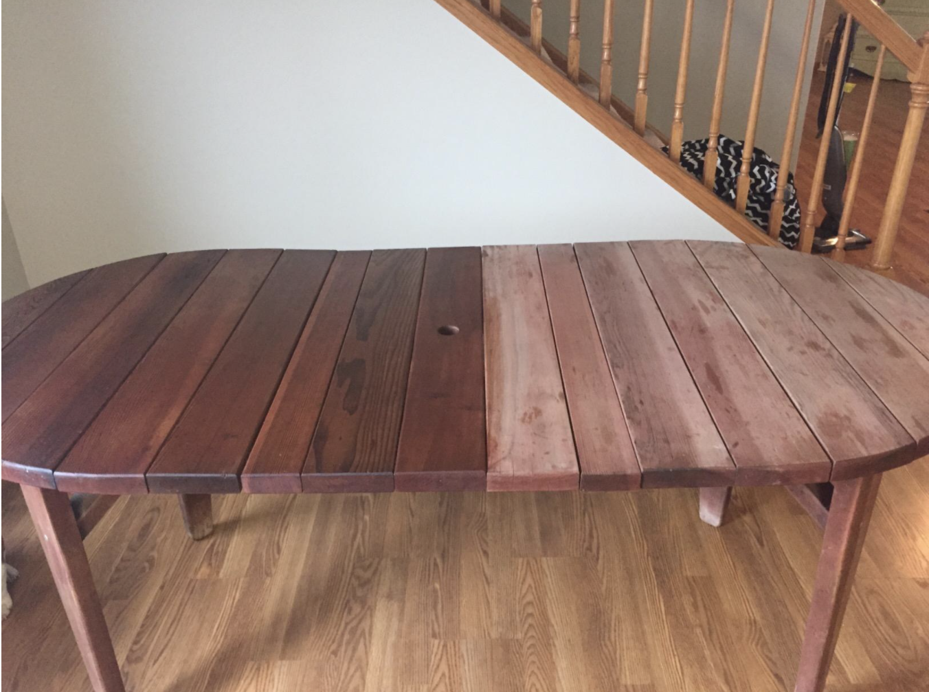 a reviewer photo of a table with the before on the right side of the photo and the after on the left showing a significant difference in the shade and shine of the wood