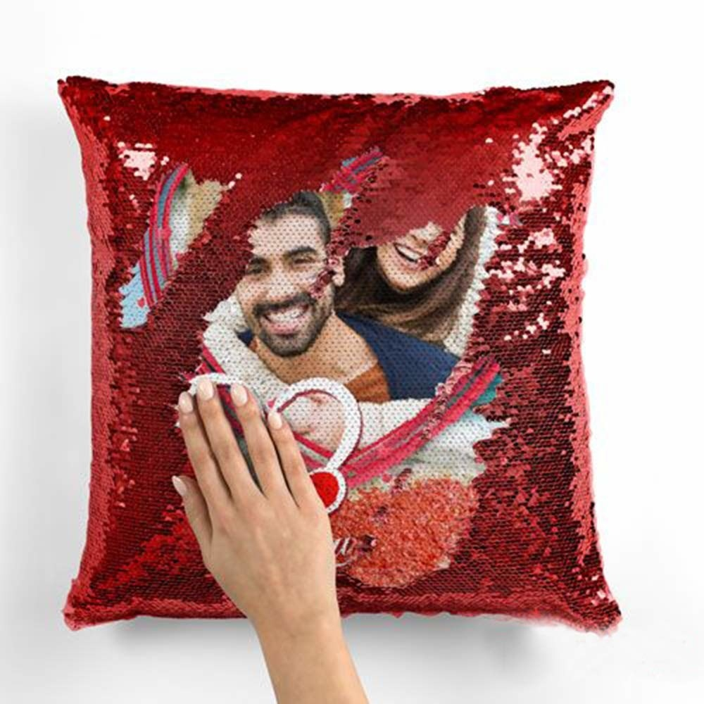 A red reversible sequin pillow with a picture of a couple