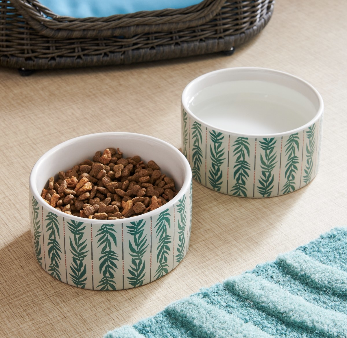 Two pet bowls with a turquoise vine pattern