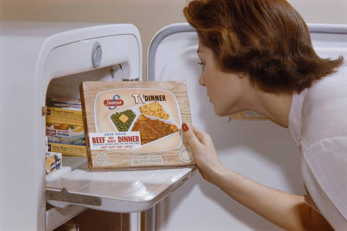 A color photo from the 1950s of a housewife opening her freezer and pulling out a Swanson TV Dinner