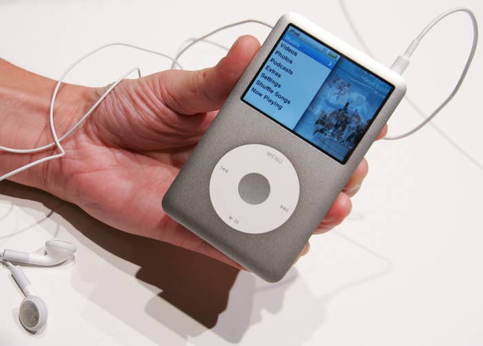 A hand holding a Classic silver iPod