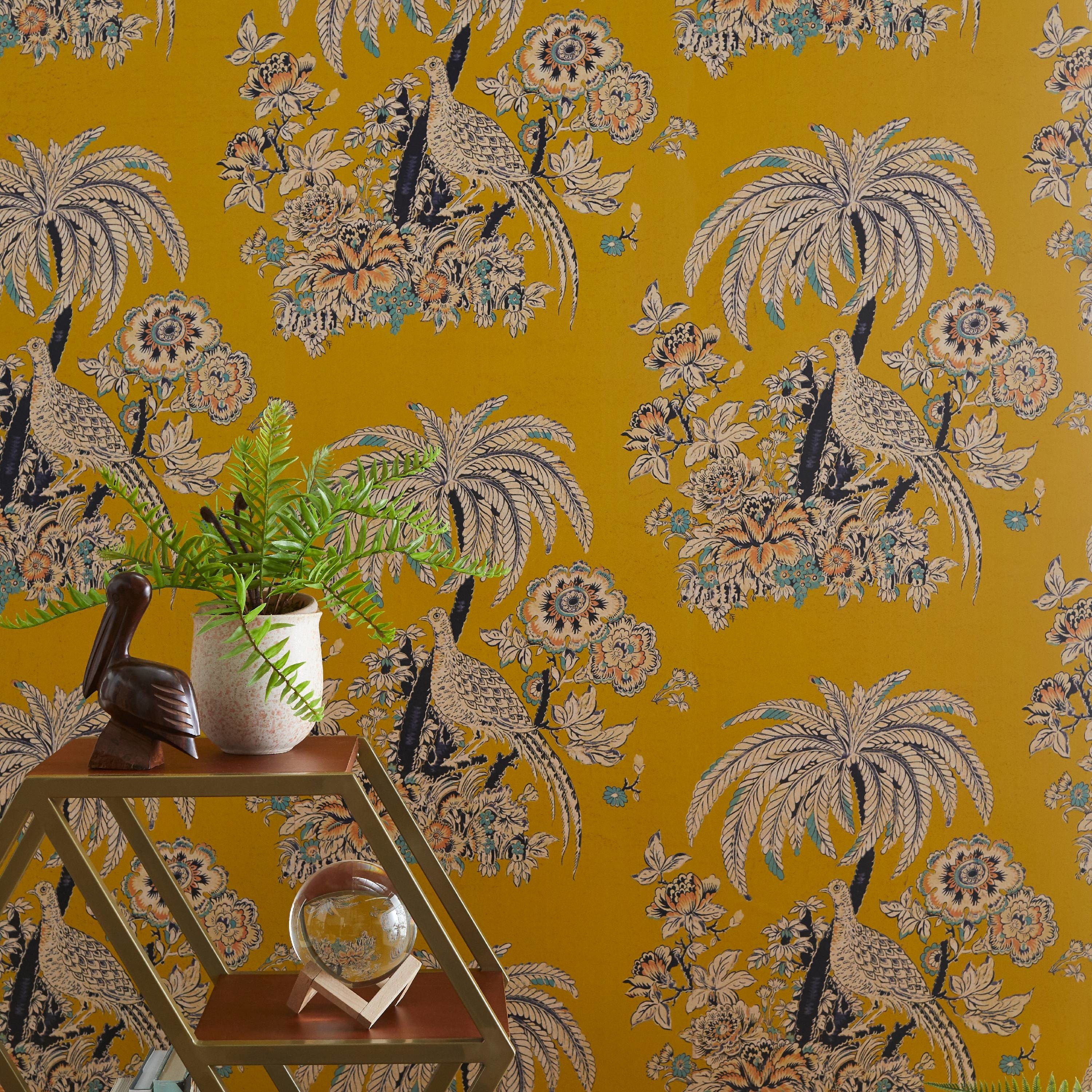 A gold-yellow wallpaper with a repeating image of a peacock by a palm tree surrounded by flowers