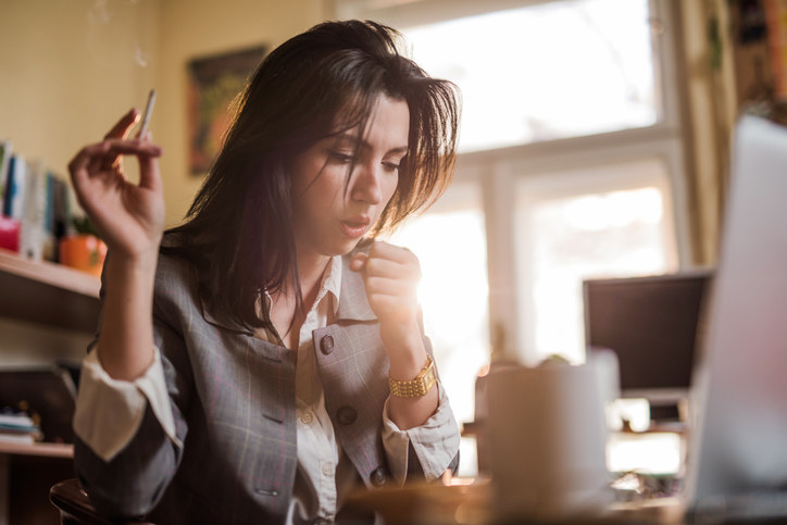 A woman holding a cigarette and coughing as she sits at her desk
