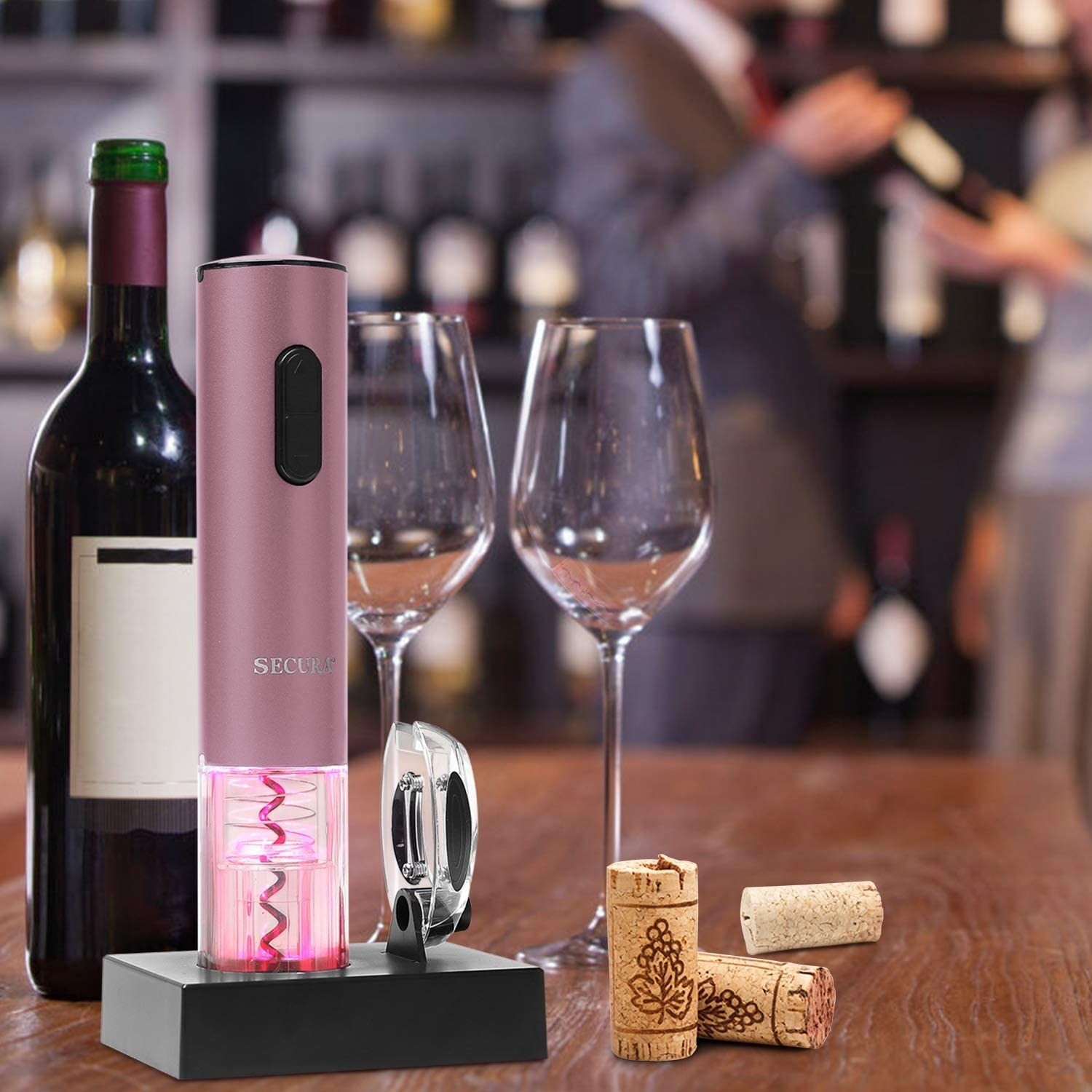 The electic wine opener on a stand next to the foil cutting device