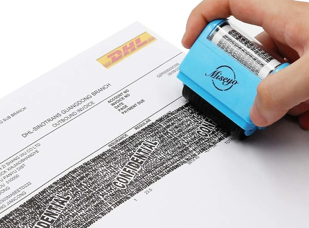 A person using the rolling stamp to cover their personal information on a document
