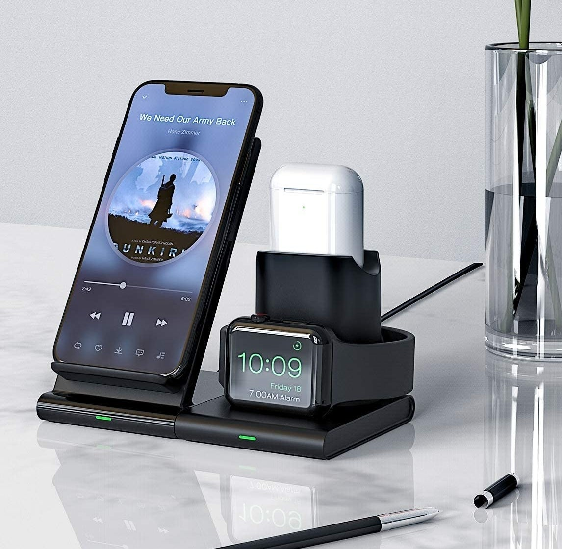 A phone, airpods case, and apple watch charging together on the charging platform