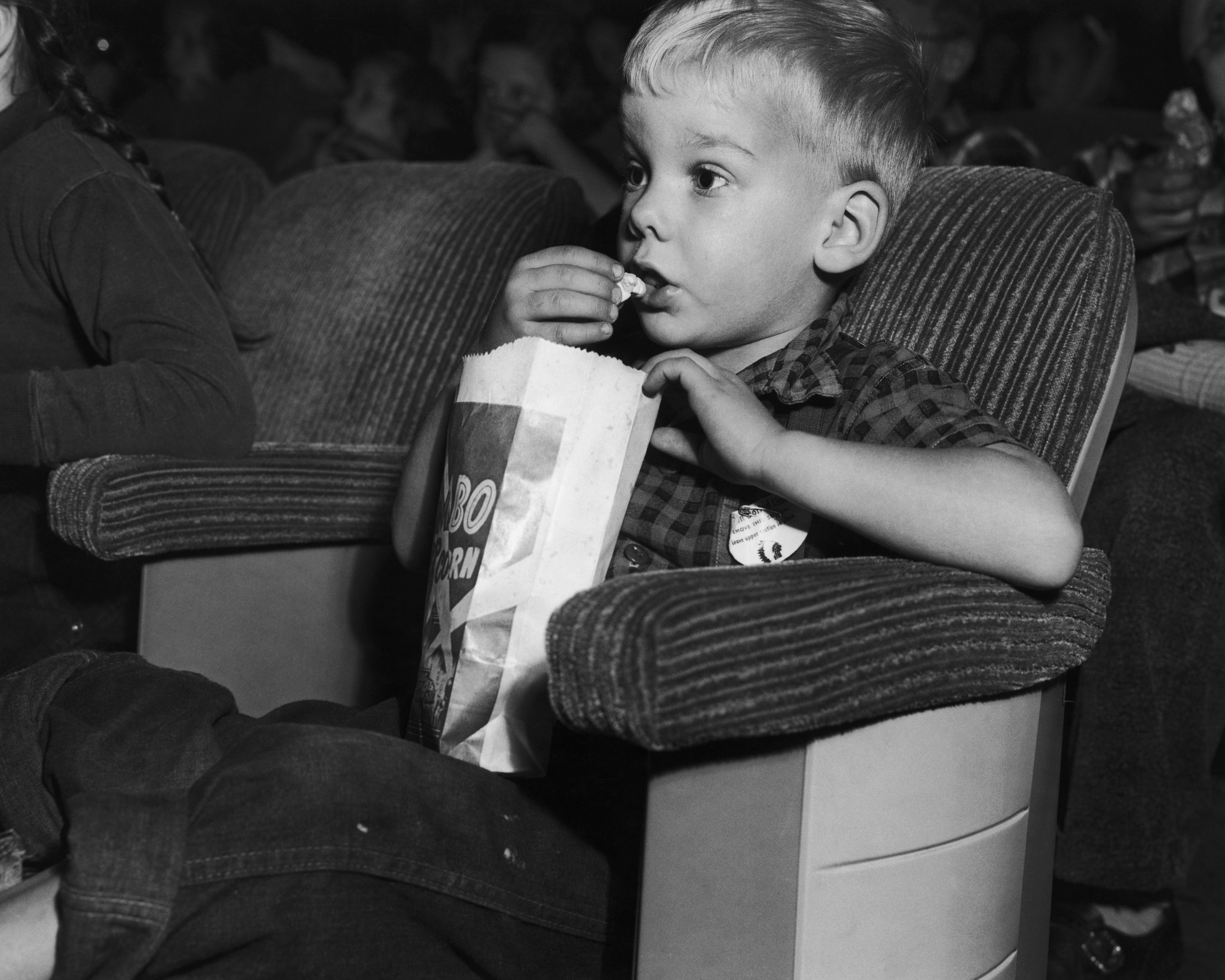 With eyes glued to the screen, a young boy eats a bag of popcorn while attending a Saturday matinee at the movie theater