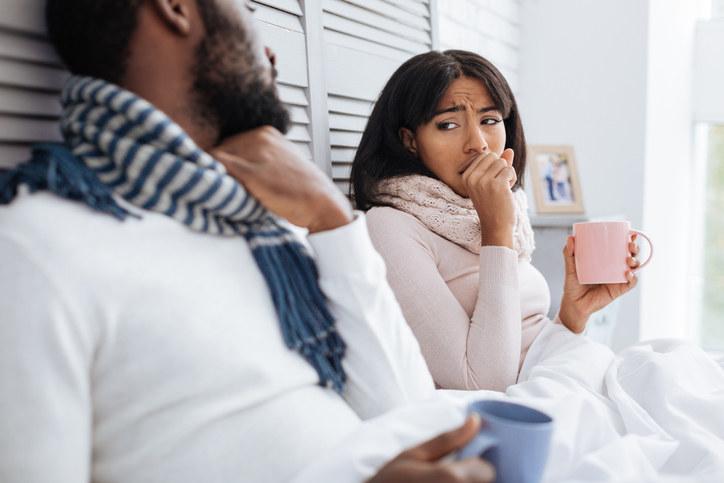 A man, who's holding a coffee mug, and a woman, who's coughing and also. holding a mug, sitting in bed