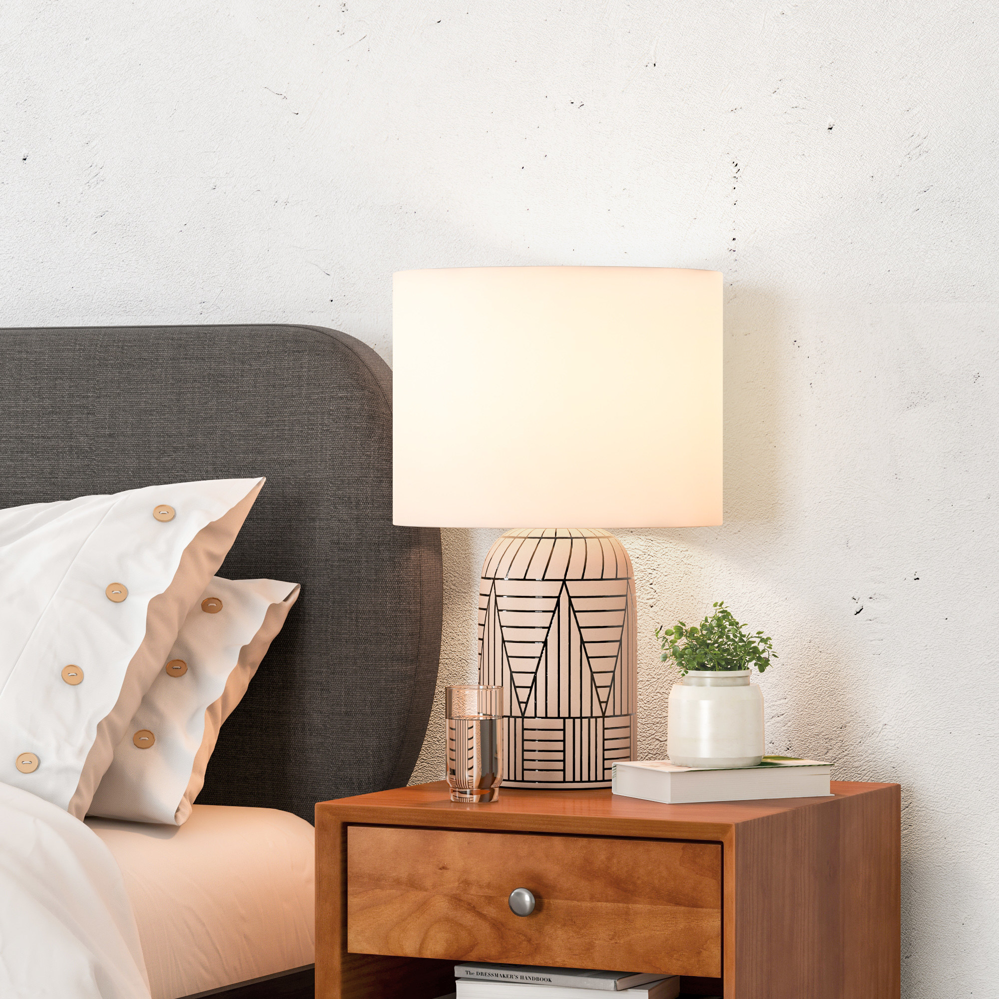 A beige ceramic table lamp with a black line pattern and a white shade