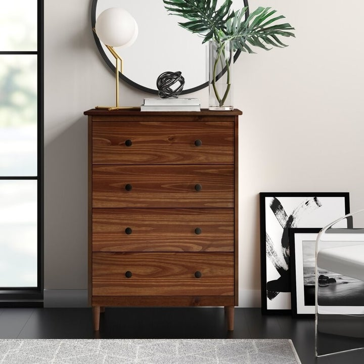 four-drawer wood chest in brown with two round black knobs on each drawer