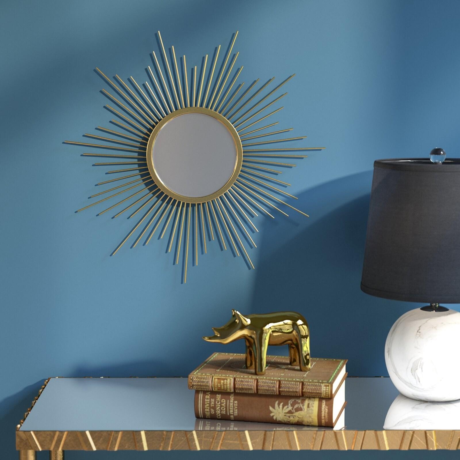 gold accent sunburst mirror on a blue wall