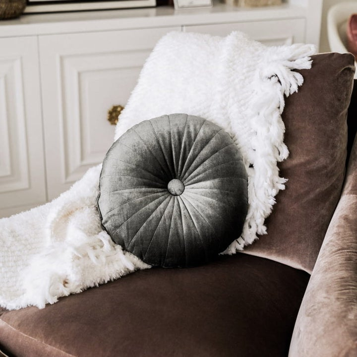 Gray tufted accent pillow on brown arm chair