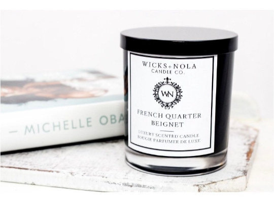 """candle with minimalist label of """"French Quarter Beignet"""" beside Michelle Obama's book"""