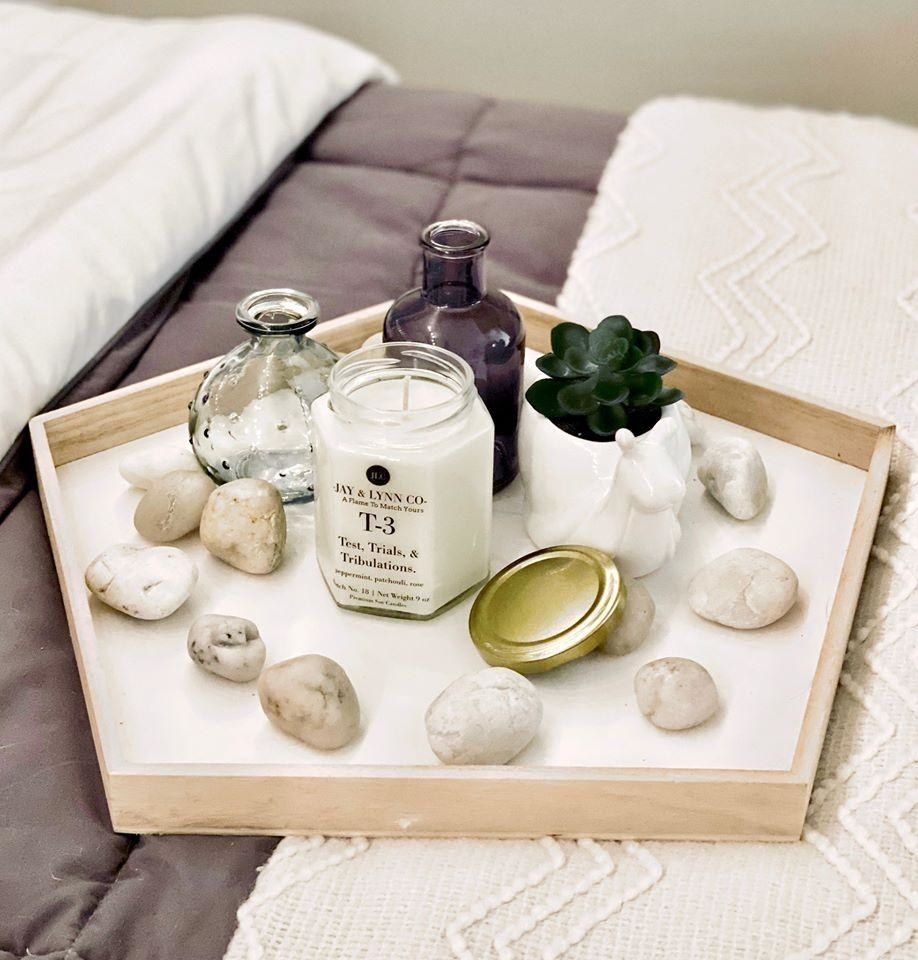 bed with a tray on it containing a candle plus a succulent and rocks